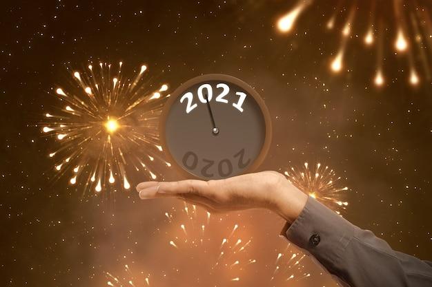 Biznesmen ręka trzyma zegar czeka na 2021. szczęśliwego nowego roku 2021