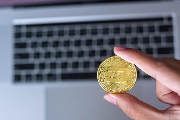Biznesmen ręka trzyma złotą monetę dash cryptocurrency nad klawiaturą laptopa, crypto to cyfrowe pieniądze w sieci blockchain