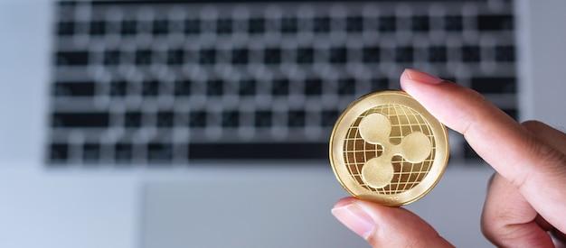 Biznesmen ręka trzyma złotą monetę kryptowaluty ripple (xrp) na klawiaturze laptopa, moneta ripple. crypto to cyfrowe pieniądze w sieci blockchain