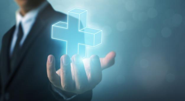 Biznesmen ręka trzyma znak plus wirtualny oznacza oferować pozytywne rzeczy (takie jak korzyści, rozwój osobisty, sieć społecznościowa)