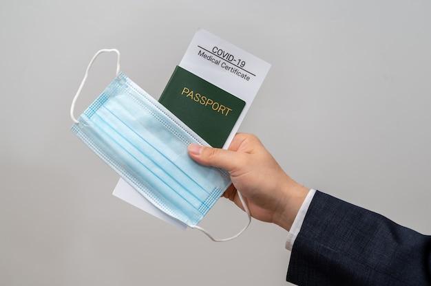 Biznesmen ręka trzymająca świadectwo zdrowia, paszport i maskę medyczną covid-19. koncepcja biznesowa po covid-19.