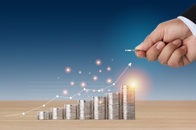 Biznesmen ręka układająca monety rośnie z wykresem wzrostu na niebieskim tle drewnianego stołu