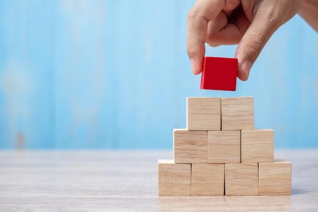 Biznesmen ręka umieszcza czerwonego drewnianego blok na budynku lub ciągnie.