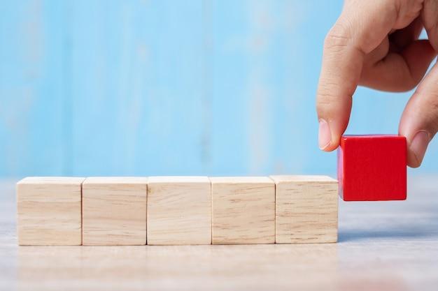 Biznesmen ręka umieszcza czerwonego drewnianego blok na budynku lub ciągnie