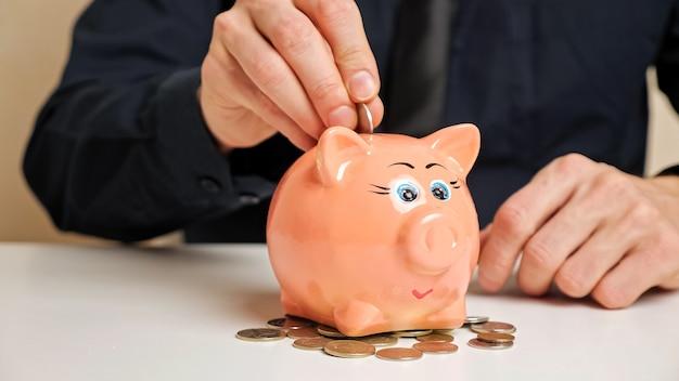 Biznesmen ręka w czarnej koszuli trzyma małą monetę i rzuca do ślicznej różowej skarbonki stojącej na porozrzucanych żetonach na białym stole zbliżenie