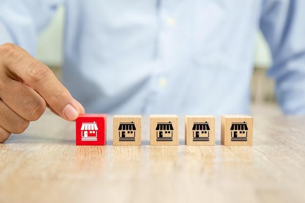 Biznesmen ręka wybiera drewnianego blogu z franczyzy ikon marketingowym sklepem.