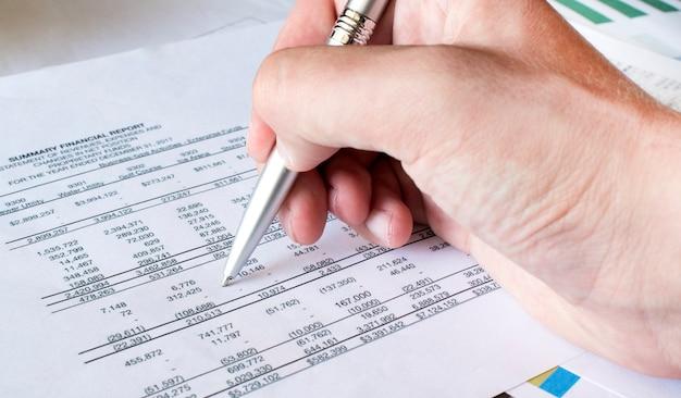 Biznesmen ręka z piórem na finansowym papierze. analiza. pojęcie