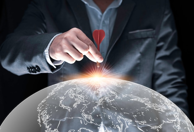 Biznesmen ręki mienia i trowing czerwona strzałka celować deskę na czarnym tle i światowej mapie biznesu i inwestyci celu pojęcie.
