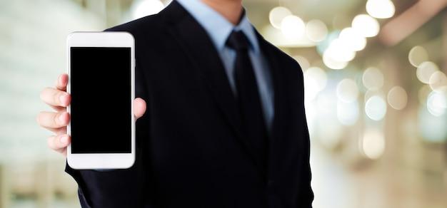 Biznesmen ręki mienia smartphone z pustym miejscem na parawanowym pokazie nad plamy tłem