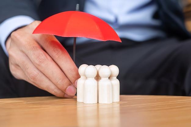 Biznesmen ręki trzymającej parasol i okładka drewniane z tłumu pracowników
