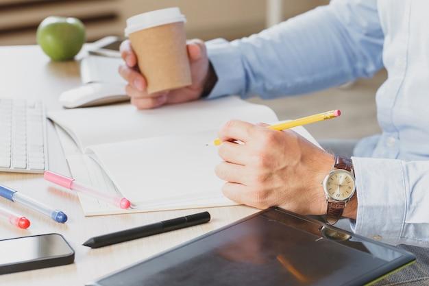 Biznesmen ręki z pióra writing notatnikiem na biurowego biurka stole