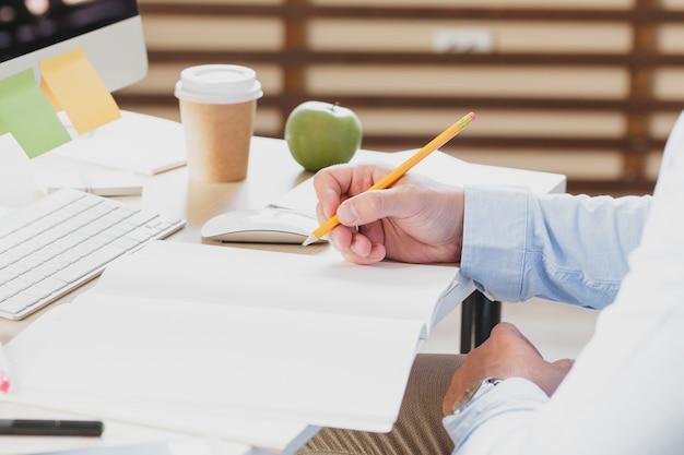 Biznesmen ręki z pióra writing notatnikiem na biurowym stole, biznesowy pojęcie,