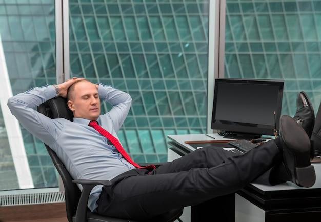 Biznesmen relaks w biurze z butami na biurku wewnątrz budynku biurowego