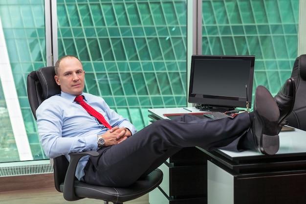 Biznesmen relaks w biurze z butami na biurku