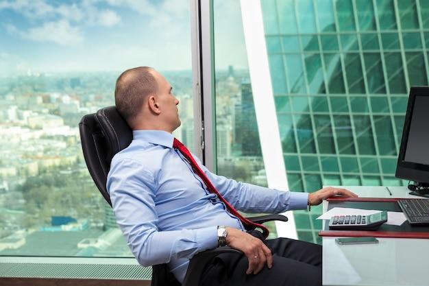 Biznesmen relaksujące myślenie patrząc przez okno wewnątrz budynku biurowego