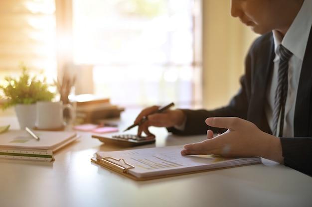 Biznesmen robi finanse i kalkuluje na biurku o kosztu w domowym biurze.