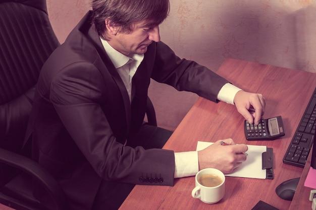 Biznesmen robi obliczenia, spisuje i pije kawę