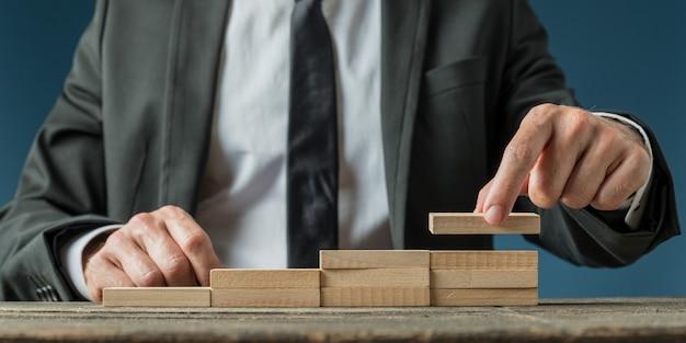 Biznesmen robi schody, takie jak struktura drewnianych kołków w koncepcyjny obraz postępu i promocji biznesu.