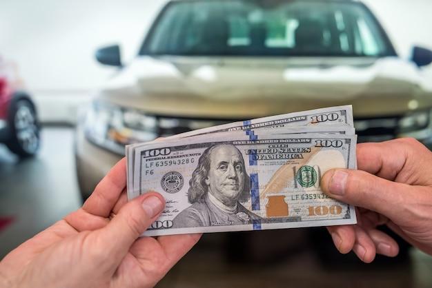 Biznesmen robi zakup lub wynajem samochodu, dając dolara sprzedawcy