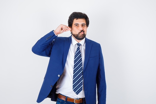 Biznesmen rozciąganie ucha i sapiąc policzki w formalnym garniturze i wygląda zabawnie. przedni widok.