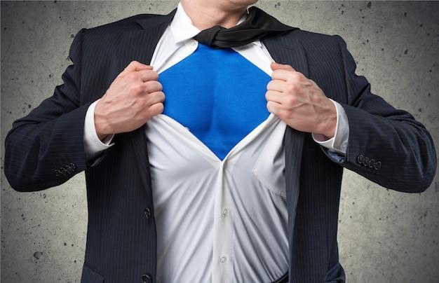 Biznesmen rozdziera na sobie koszulę, aby pokazać, że jest supermanem