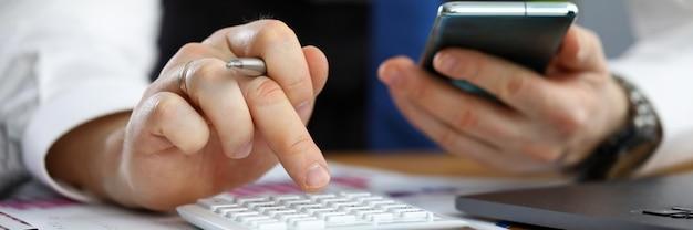 Biznesmen rozlicza na kalkulatorze z telefonem