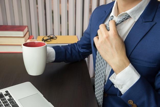Biznesmen rozluźnia krawat prowadzi filiżankę kawy
