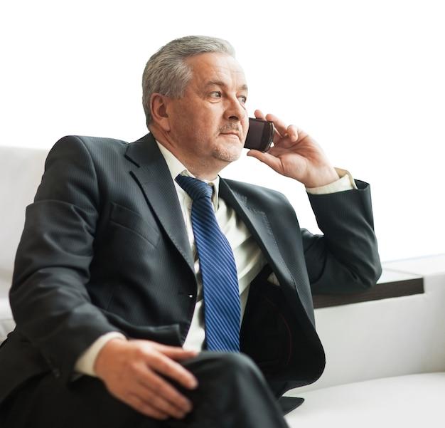 Biznesmen rozmawia na smartfonie w biurze.
