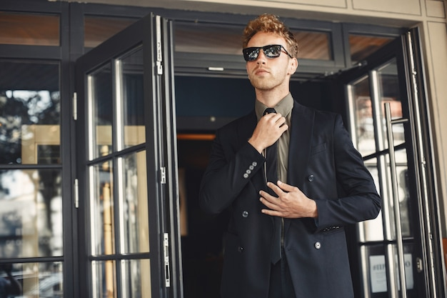 Biznesmen rozmawia przez telefon i trzyma folder w dłoniach. mężczyzna w okularach przeciwsłonecznych.