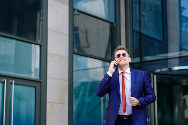 Biznesmen rozmawia przez telefon i uśmiecha się.