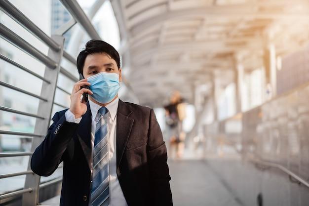 Biznesmen rozmawia przez telefon komórkowy i nosi maskę medyczną podczas pandemii koronawirusa w mieście