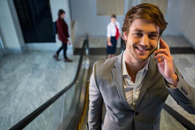 Biznesmen rozmawia przez telefon komórkowy na schodach