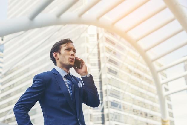 Biznesmen rozmawia przez telefon komórkowy przeciwko budynku na zewn? trz.
