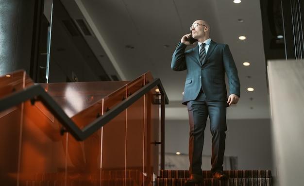 Biznesmen rozmawia przez telefon komórkowy, stojąc na szczycie schodów w centrum biznesowym. przystojny