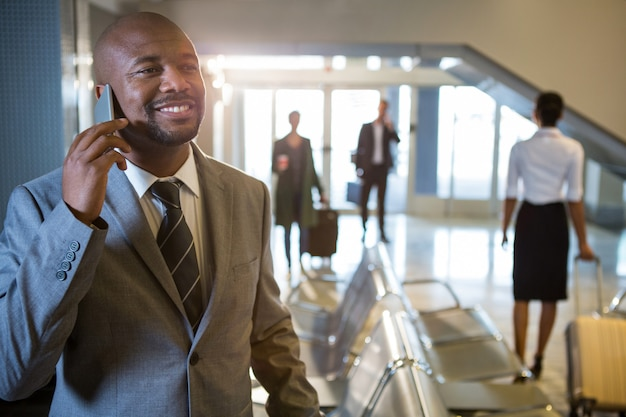 Biznesmen rozmawia przez telefon komórkowy w poczekalni
