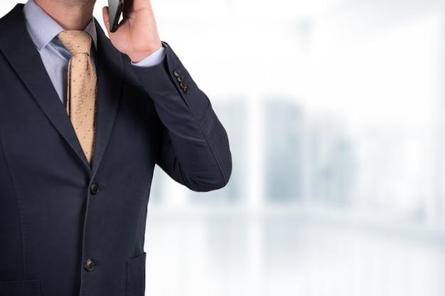 Biznesmen rozmawia przez telefon komórkowy z niewyraźnym tłem biurowym