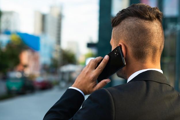 Biznesmen rozmawia przez telefon na zewnątrz