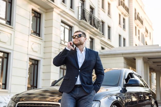 Biznesmen rozmawia przez telefon obok samochodu na scenie ulic miasta