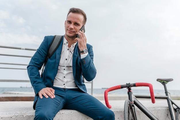 Biznesmen rozmawia przez telefon obok swojego roweru na zewnątrz