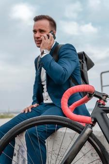 Biznesmen rozmawia przez telefon obok swojego roweru