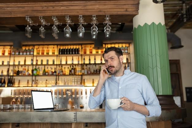 Biznesmen rozmawia przez telefon w kawiarni.