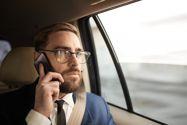 Biznesmen rozmawia przez telefon w taksówce