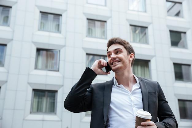 Biznesmen rozmawia przez telefon z kawą