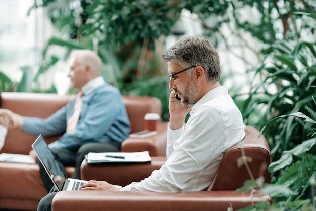 Biznesmen rozmawia ze smartfonem i pracuje na laptopie