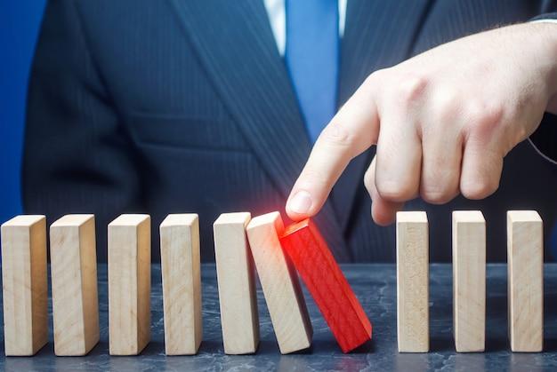 Biznesmen rozpoczyna proces spadania kostek domina.