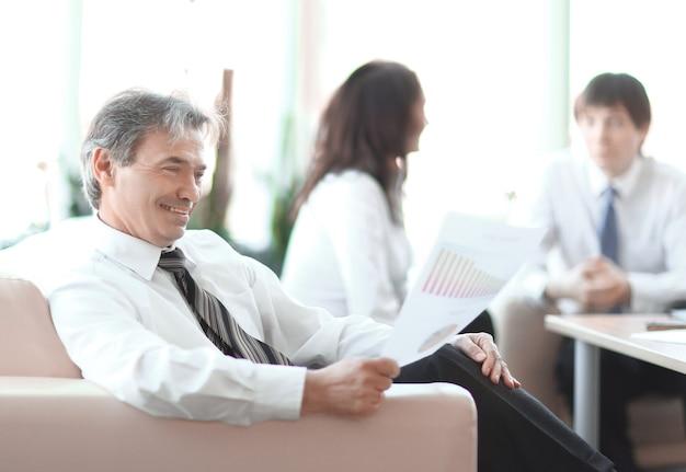Biznesmen rozważa dokument siedzący w nowoczesnym biurze.zdjęcie z miejscem na kopię