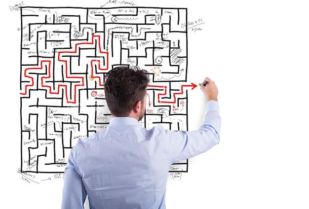 Biznesmen rozwiązuje złożony labirynt z wieloma trudnościami