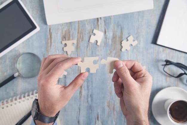 Biznesmen rozwiązywania zagadek przy biurku