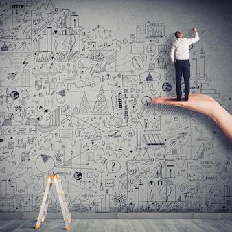 Biznesmen rysuje grafikę i statystyki na ścianie