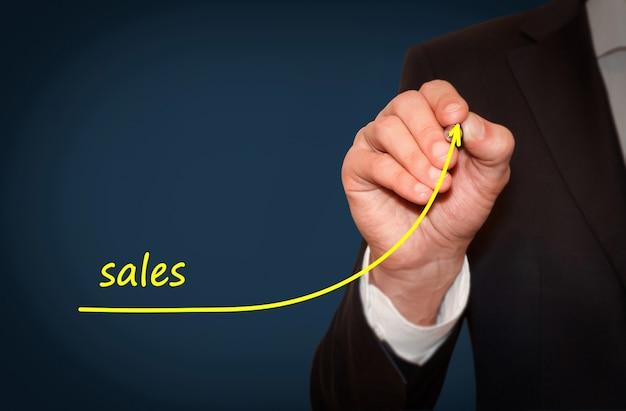 Biznesmen rysuje rosnącą linię symbolizującą rosnącą sprzedaż firmy